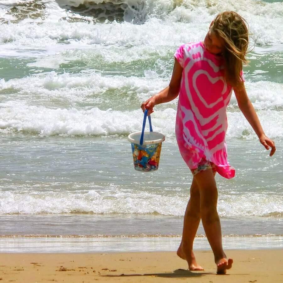 Mädchen mit Eimer am Strand